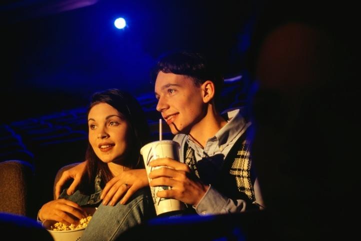 Ilustração: casal come pipoca no escurinho do cinema